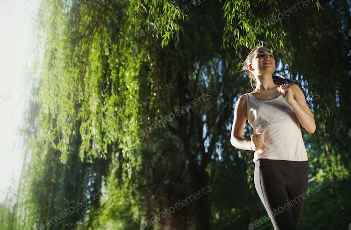 Beautiful female jogger running outside