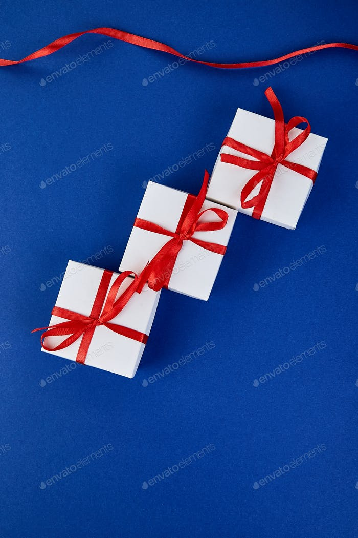 Luxury white gift boxes with red ribbon