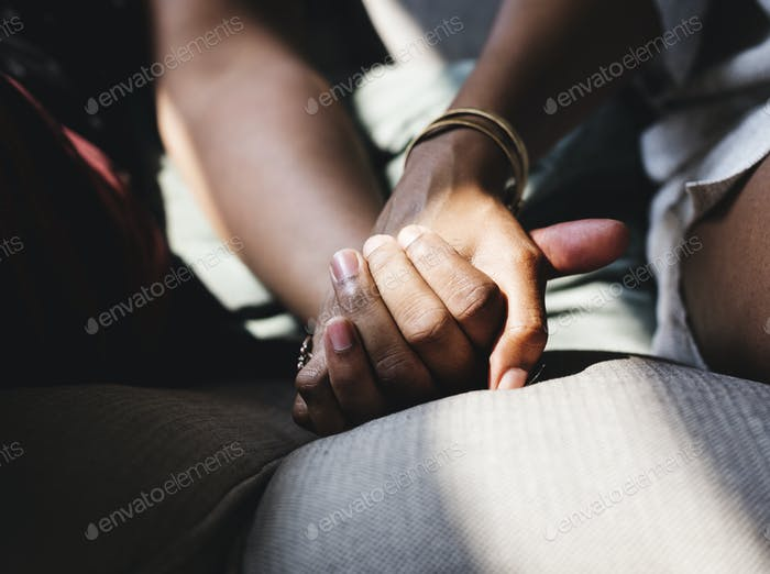 Closeup of couple holding hands