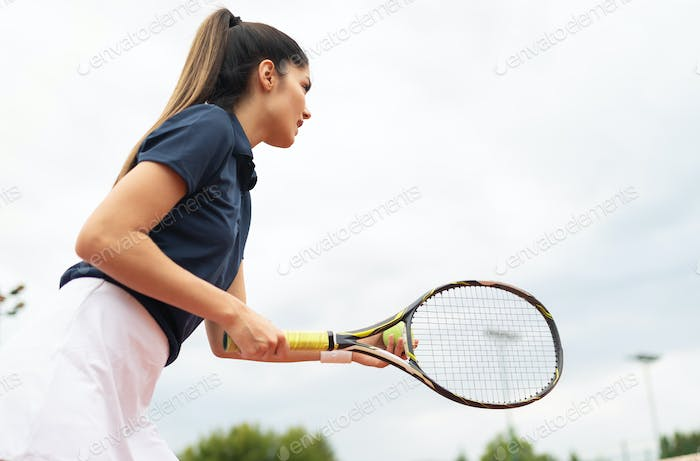 Young happy woman playing tennis at tennis court