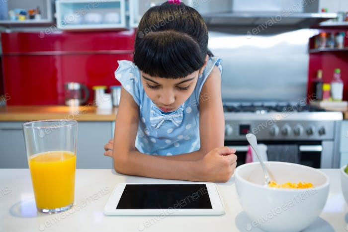 Girl looking at tablet computer while sitting with breakfast