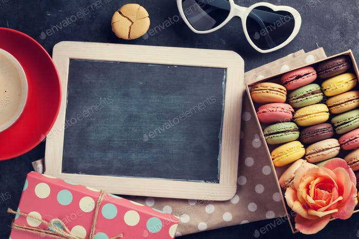 Colorful macaroons, coffee and blackboard