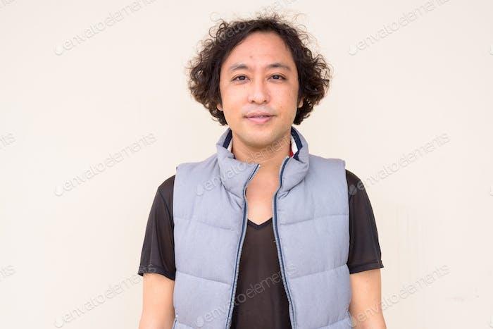 Портрет японца с кудрявыми волосами смотрит на камеру