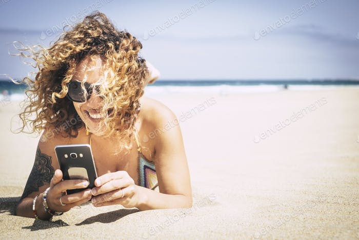 cheerful beautiful young lady smile and use cellular phone at the beach