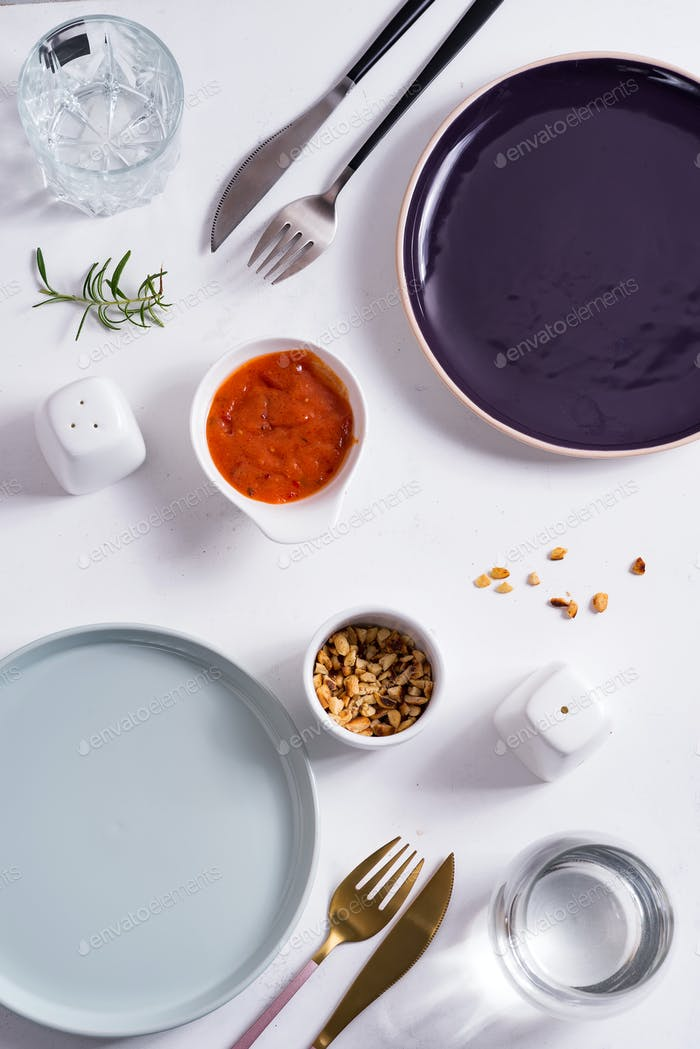 Empty round blue and purple plates with cutlery , roasted peanuts and tomato sauce on white