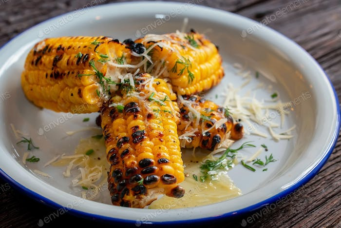 Close up grilled corn on the cob in white plate