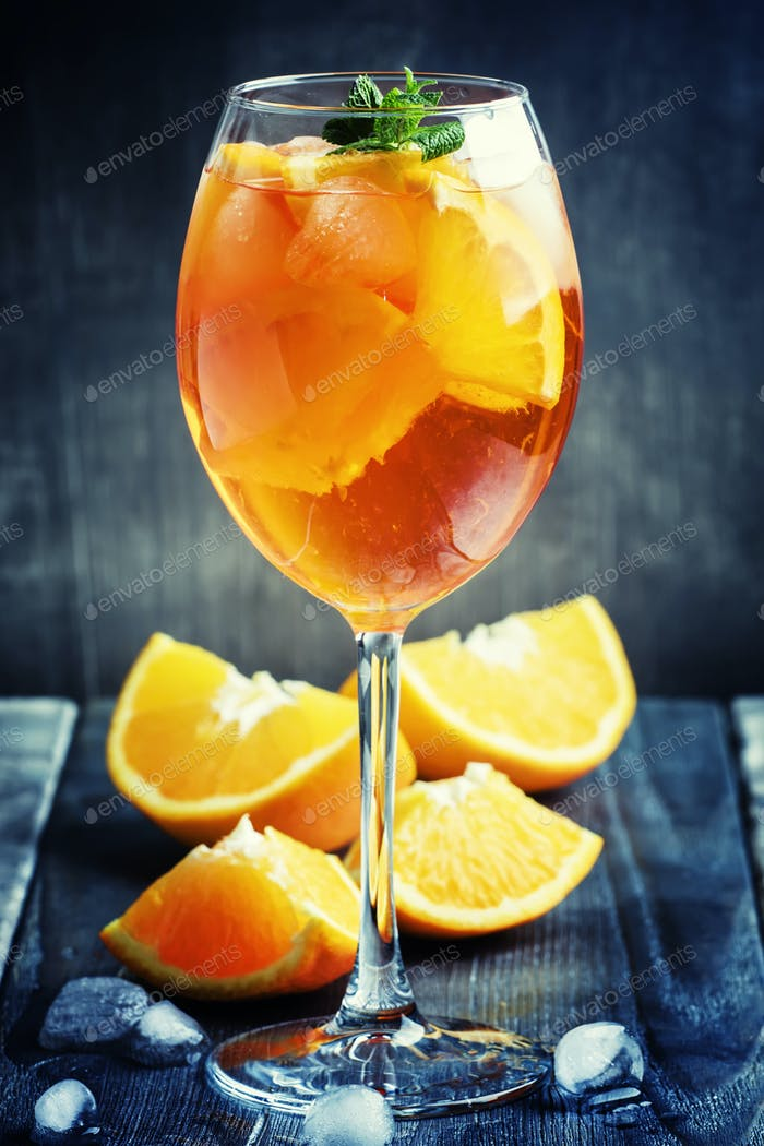 Alcohol cocktail with orange juice, fruit, bitter and ice