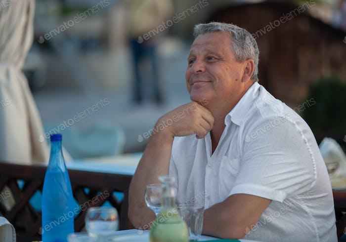 Charming reifen Mann in outdoor cafe