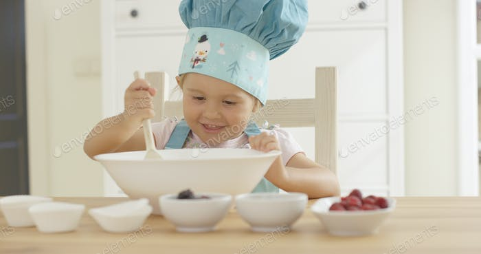 Adorable smiling toddler at mixing bowl