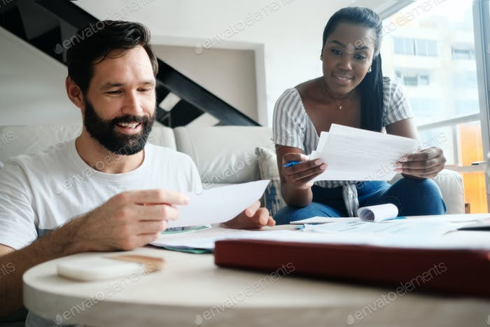 Couple Checking Bills For Home Budget