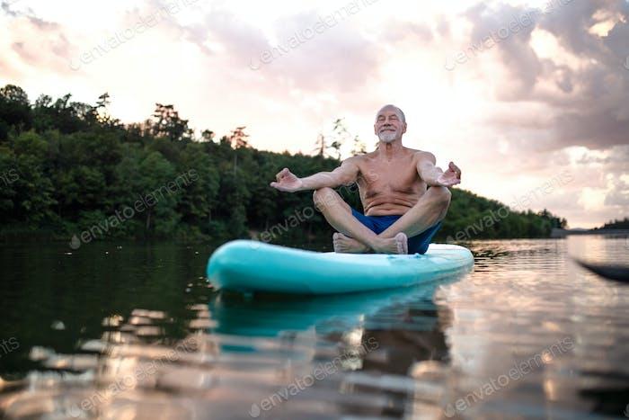 Senior man on paddleboard on lake in summer, doing yoga exercise