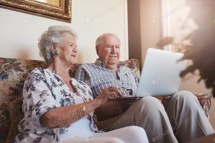 Elderly couple using laptop at home