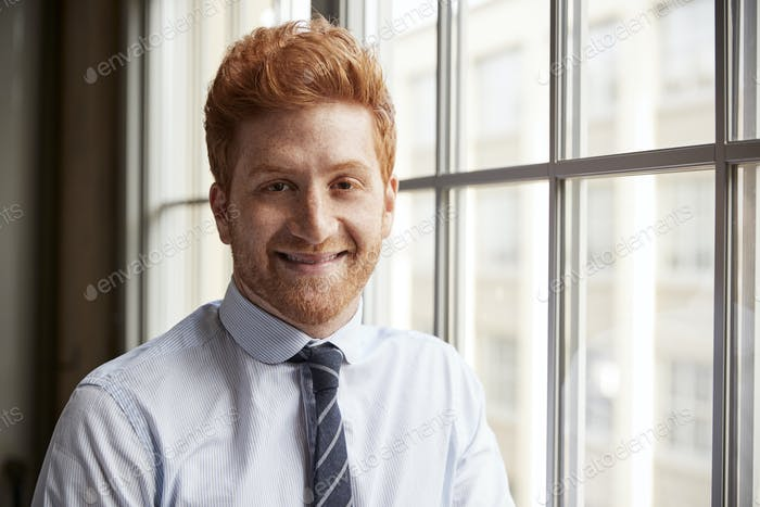 Young red haired bearded businessman smiling to camera