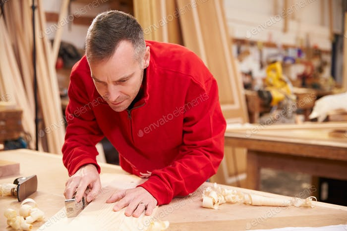 Carpenter Planing Wood In Workshop
