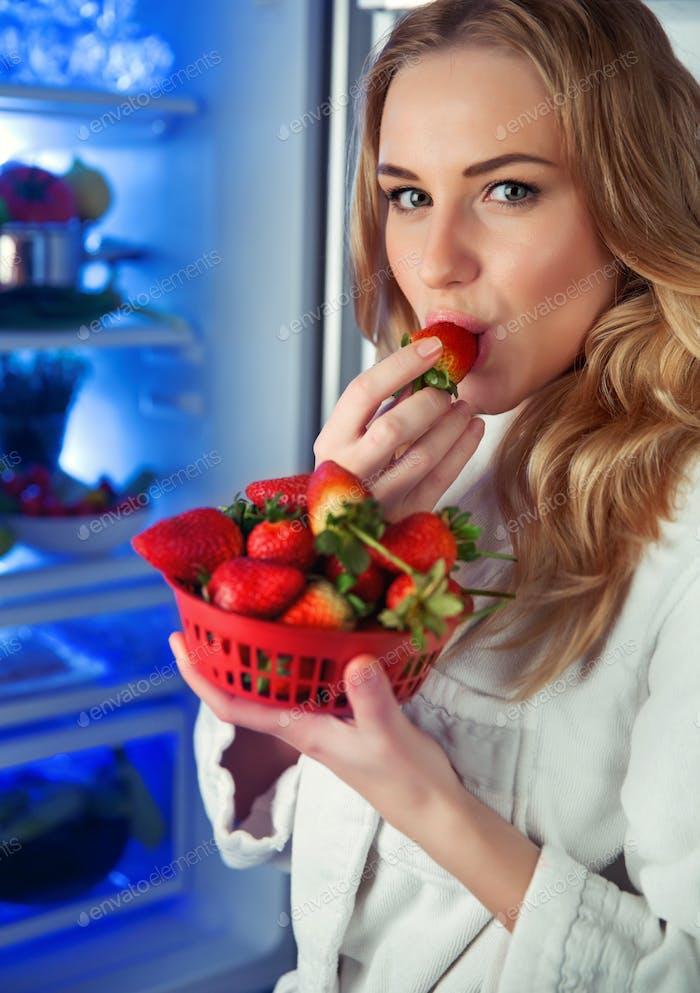 Hübsche Frau schmeckt Erdbeere