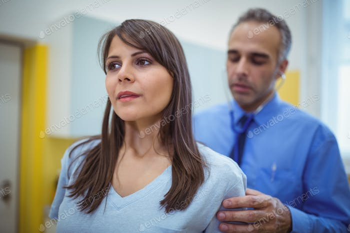 Doctor examining a female patients back