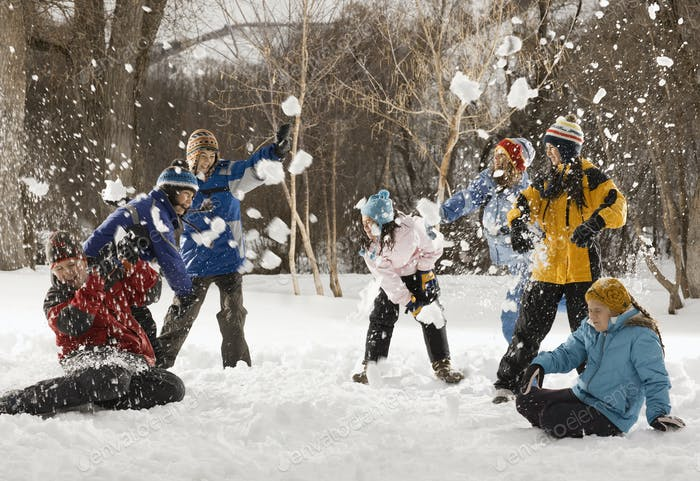 Four people outdors in hats, coats and scarves, having an energetic snowball fight.