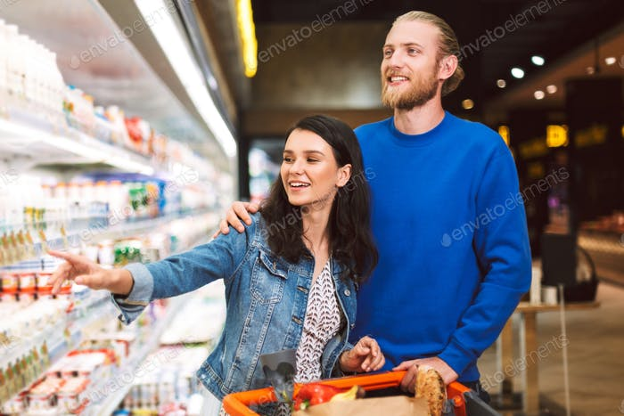 Young joyful couple with trolley full of products happily choosi