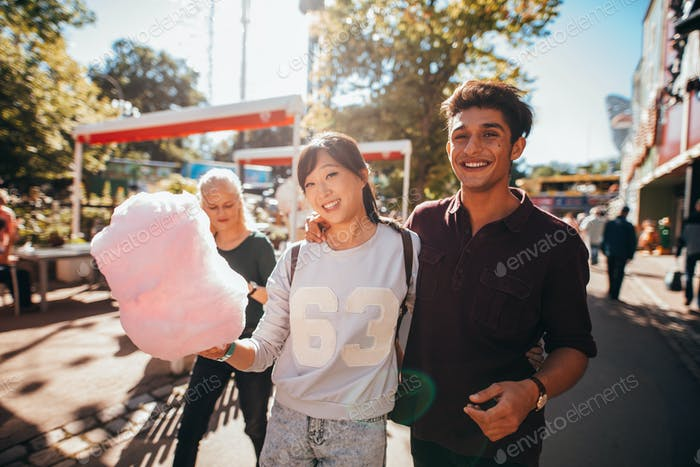 Young people with cotton candyfloss at amusement park