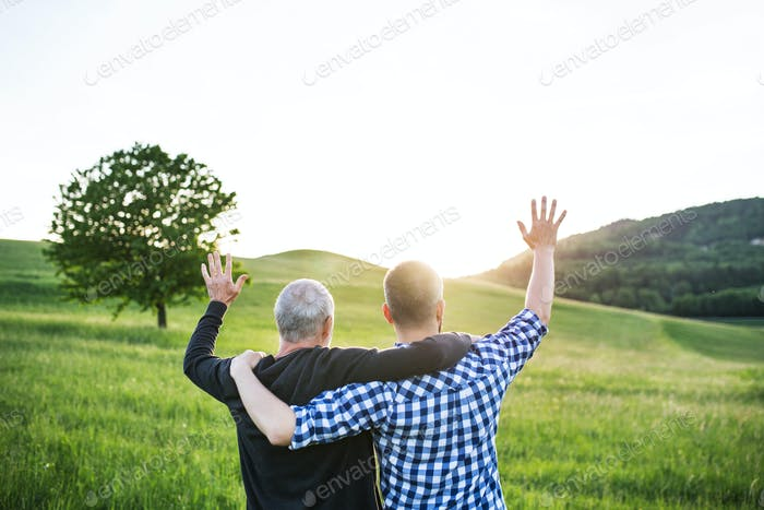 An adult hipster son with senior father on a walk in nature at sunset, arms around each other.