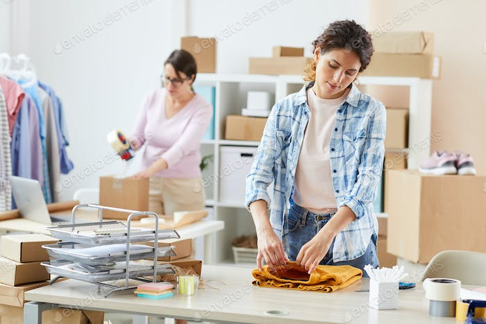 Online shop manager in shirt folding yellow sweater on desk before packing