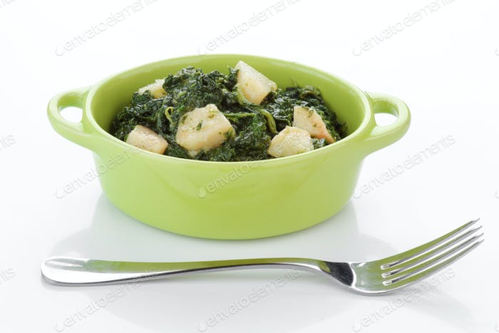 spinach stewed with potatoes in green porcelain bowl isolated on white
