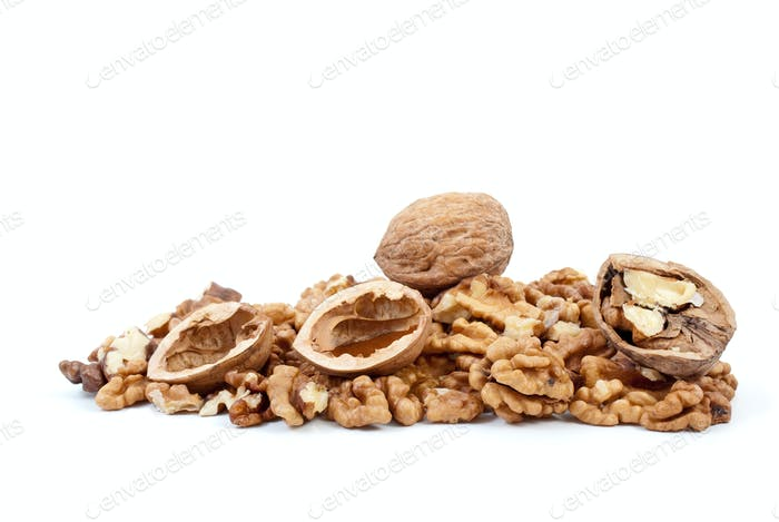 Whole and cracked walnuts with nutshells over kernels