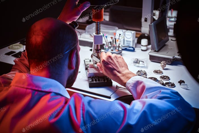 Mature watchmaker is working at his own studio.