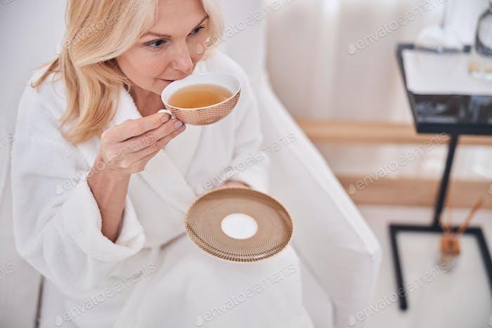 Pensive woman taking a sip of chamomile tea