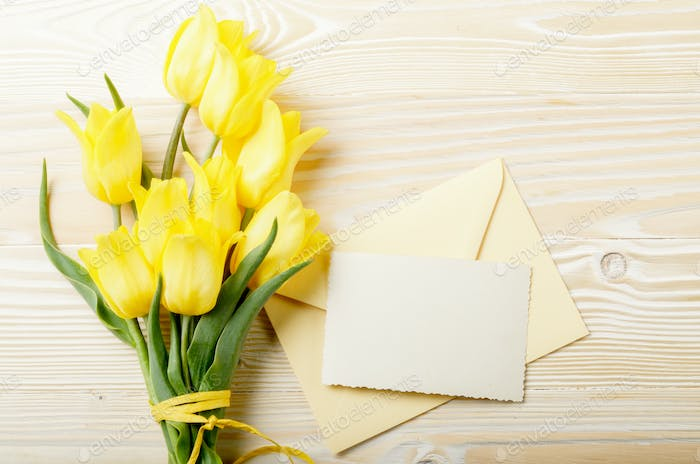 Yellow tulips near blank greeting card and envelope on natural w