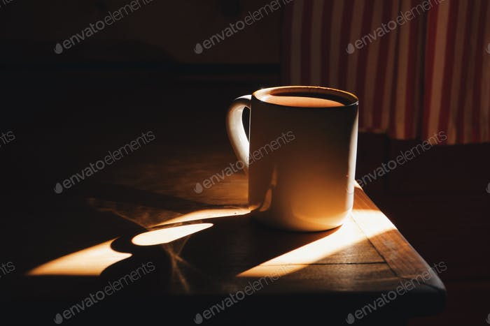 cup of coffee in a morning light, rustic wooden cottage interior