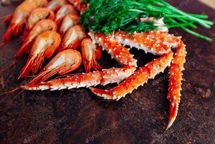Auf dem Tisch sind Garnelen, Krabben, Zitrone und Kräuter. Tabelle von rötlicher Farbe.