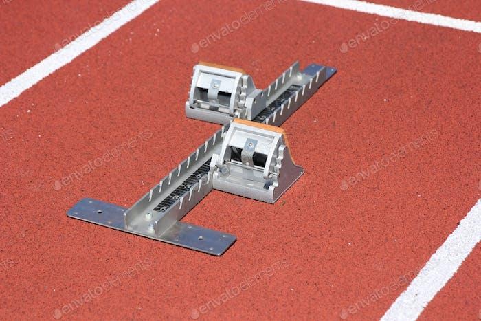 Athletics starting blocks on race red track