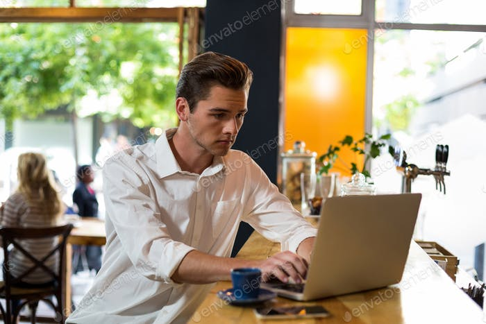 Man using laptop at a counter