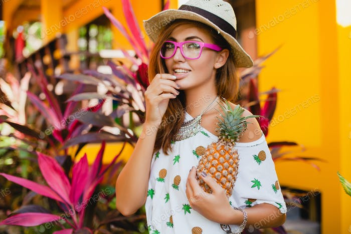 attractive smiling woman on vacation holding pineapple