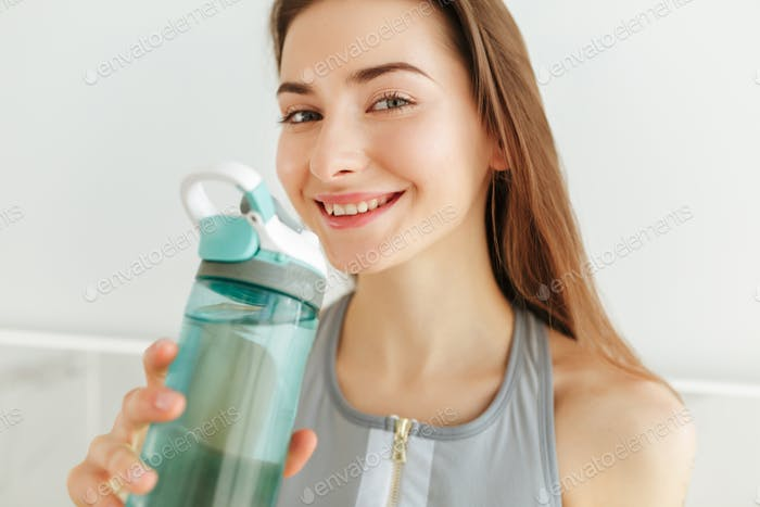 Young lady in sporty top happily looking in camera with earphones and bottle of water on kitchen