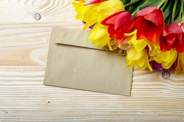 Bunte Tulpen und leerer Umschlag auf natürlichem Holzhintergrund