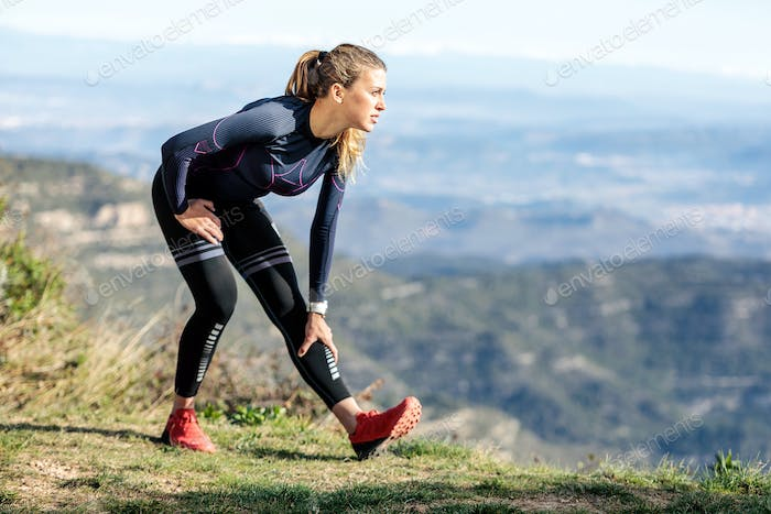 Trail runner stretching while looking landscape from mountain pe