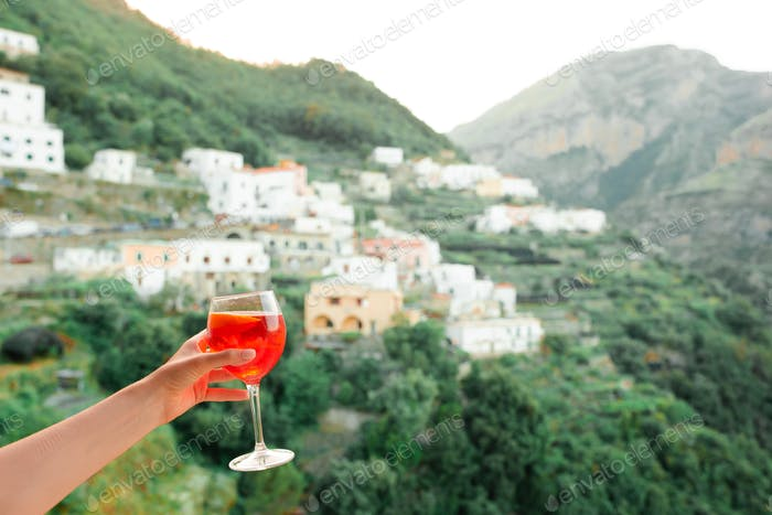 Female hand holding glass with Spritz Aperol alcohol drink background of beautiful old italian