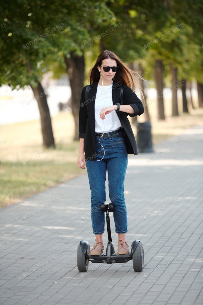 Young elegant businesswoman looking at wristwatch while riding on gyroscope
