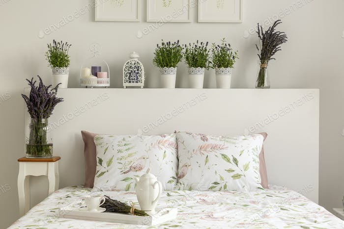 Lavender bedroom interior with a bed, pillows, wooden tray with