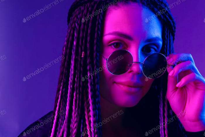 Stylish young woman with braids wearing sunglasses against purple background