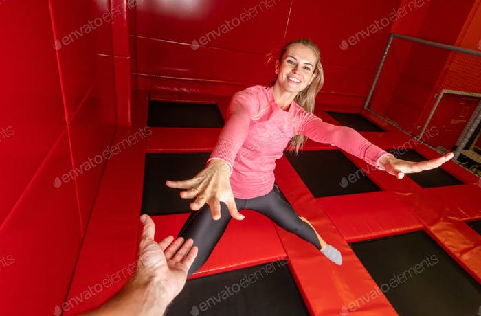 Fit young woman jumping on trampoline in fitness gym
