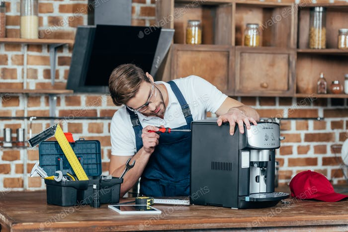 professional young worker in eyeglasses and protective workwear fixing coffee machine