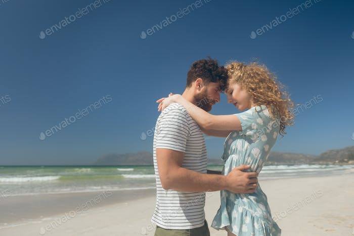 Romantic couple standing at beach on a sunny day