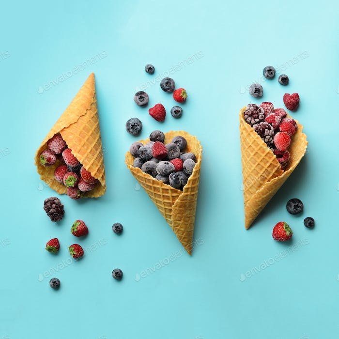 Frozen berries - strawberry, blueberry, blackberry, raspberry in waffle cones on blue background