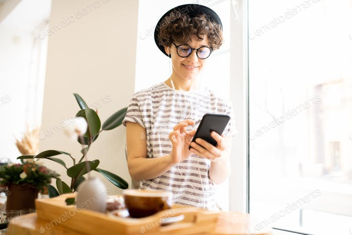 Modern woman using smartphone in cafe