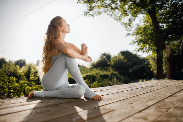 Young woman is practising yoga sitting on a wooden podium in the garden with folded hands near the
