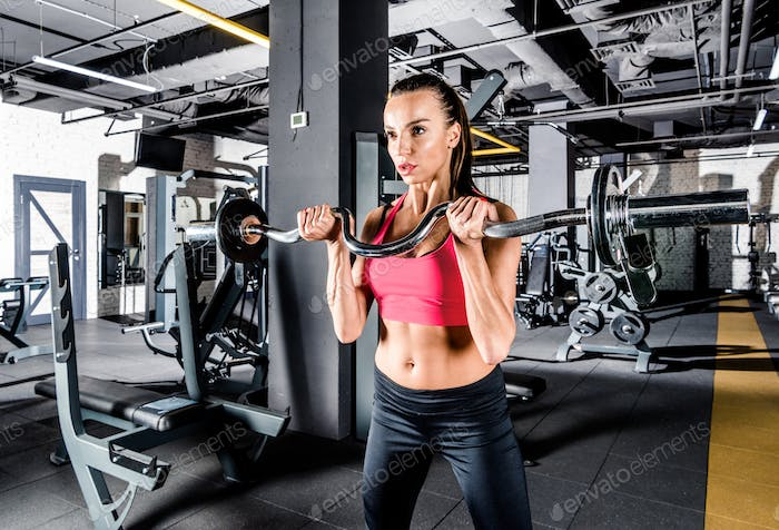 Young sportive woman exercising with barbell in gym
