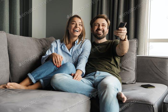 Foto de la alegre pareja viendo la televisión y usando el control remoto